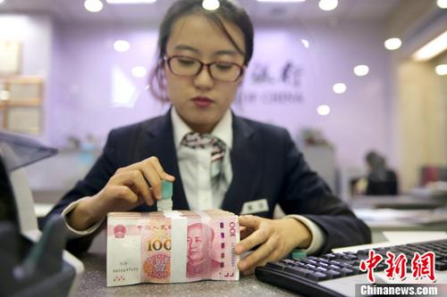 资料图:银行工作人员清点货币。记者 张云 摄
