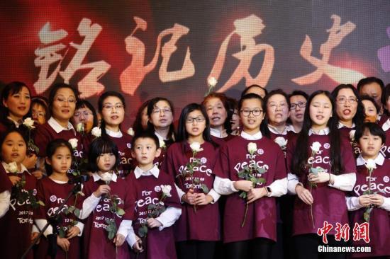 """当地时间12月9日,加拿大安大略省各界华人共同举办的""""南京大屠杀80周年追思会""""在多伦多举行。来自华人社区及其他多个族裔社区的逾千名代表参加此次主题为""""铭记历史,祈愿和平""""的追思会。图为社区人士与孩子们在追思会上合唱《让世界充满爱》。 <a target='_blank' href='http://www.chinanews.com/'>中新社</a>记者 余瑞冬 摄"""