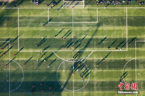 """资料图:周末时分,很多在中国生活的""""老外""""摩拳擦掌,去绿茵场享受足球的快乐。 <a target='_blank' href='http://www.nihaopiao.com/'>中新社</a>记者 泱波 摄"""