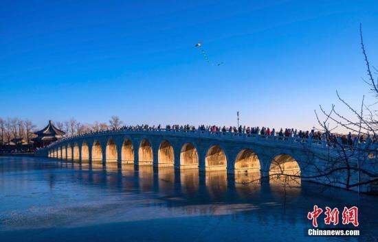 """资料图:北京颐和园十七孔桥再现""""金光穿孔""""景象,上千名游客和摄影爱好者在南湖岛拍摄这一冬日奇观。中新社记者 张炜 摄"""