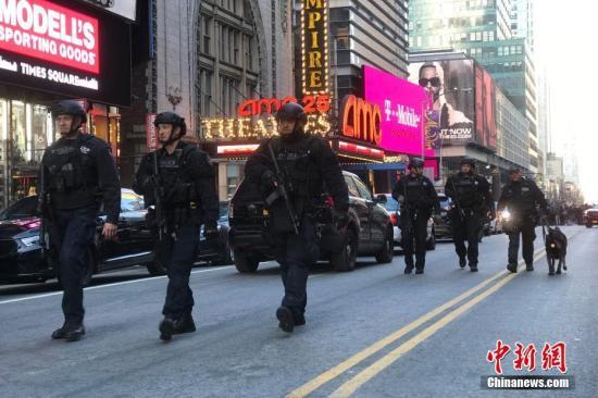 当地时间12月11日,位于纽约曼哈顿42街第八大道的纽约港务局巴士总站外的持枪警察。当日早晨,该站发生爆炸,4人受伤,该站距纽约时报广场不远。受此影响,数条地铁和公交线路停运。 中新社记者 廖攀 摄