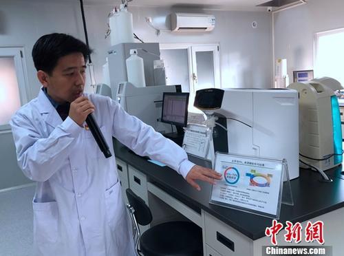 """12月12日,环保部组织的""""打赢蓝天保卫战""""大型主题采访活动来到北京市环境保护监测中心,图为中心工作人员向记者介绍北京市PM2.5监测情况。最新数据显示,截至11月底,今年北京市PM2.5累计浓度为每立方米58微克,同比降幅13.4%,较2013年同期下降35.6%。<a target='_blank' href='http://www.chinanews.com/'>中新社</a>记者 阮煜琳 摄"""