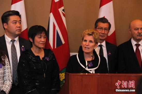 """在南京大屠杀80周年之际,当地时间12月13日,加拿大安大略省省议会举行南京大屠杀纪念活动。图为安省省长韦恩(中)受邀出席在安省议会大楼内举行的一场纪念会,并表示支持华人社区开展南京大屠杀纪念活动。这是今年10月26日该省省议会通过华人省议员黄素梅(左二)提出的""""将每年12月13日设立为南京大屠杀纪念日""""动议后,该省官方场合首次正式举行南京大屠杀纪念活动。安大略省是首个设立南京大屠杀纪念日的西方国家省份。中新社记者 余瑞冬 摄"""