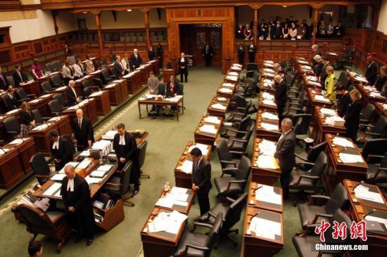 """在南京大屠杀80周年之际,当地时间12月13日,加拿大安大略省省议会举行南京大屠杀纪念活动。图为安省议会议事大厅内全体起立,为南京大屠杀数十万死难者默哀。这是今年10月26日该省省议会通过华人省议员黄素梅提出的""""将每年12月13日设立为南京大屠杀纪念日""""动议后,该省官方场合首次正式举行南京大屠杀纪念活动。安大略省是首个设立南京大屠杀纪念日的西方国家省份。中新社记者 余瑞冬 摄"""