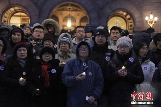 """在南京大屠杀80周年之际,当地时间12月13日,加拿大安大略省省议会举行南京大屠杀纪念活动。图为来自华人社区及其他多族裔社区的数百人当晚冒着严寒聚集在安省议会大楼前,举行烛光追思会。这是今年10月26日该省省议会通过华人省议员黄素梅提出的""""将每年12月13日设立为南京大屠杀纪念日""""动议后,该省官方场合首次正式举行南京大屠杀纪念活动。安大略省是首个设立南京大屠杀纪念日的西方国家省份。中新社记者 余瑞冬 摄"""
