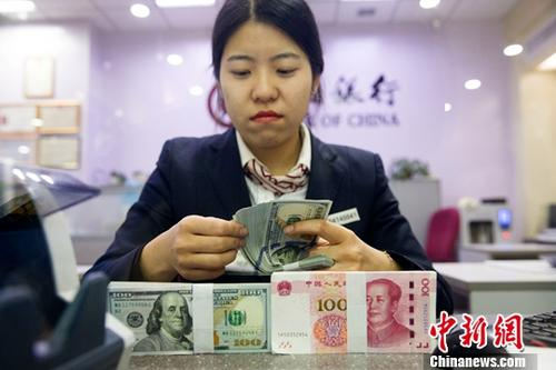 12月14日,山西太原,银行工作人员清点货币。当日,来自中国外汇交易中心的数据显示,人民币对美元汇率中间价报6.6033,较前一交易日上涨218个基点。<a target='_blank' href='http://www.chinanews.com/'>中新社</a>记者 张云 摄