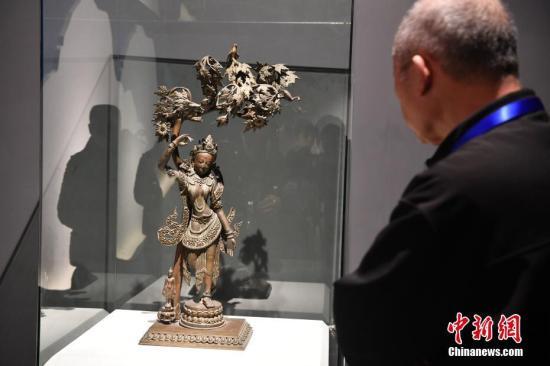 """12月15日,""""来自释迦牟尼佛的故乡――尼泊尔国家博物馆馆藏珍品中国首展""""在成都开展,30件来自尼泊尔国家博物馆的珍贵文物首次与中国民众见面。图为来自尼泊尔国家博物馆佛像吸引参观者。张浪 摄"""