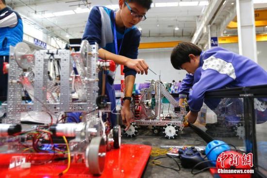 """12月16日,北京市学生机器人智能大赛举行。大赛历时2天,以""""激情创造 挑战未来""""为主题,旨在以创新实践活动为载体,为学生营造轻松、自由、开放的活动氛围,为学校开展机器人教育教学搭建成果展示与交流平台。比赛分为机器人工程挑战赛、FIRST工程挑战赛、FIRST科技挑战赛、VEX机器人工程挑战赛4个项目,来自北京市16个区县,349支队伍,1500多名中小学生参与其中。中新社记者 富田 摄"""