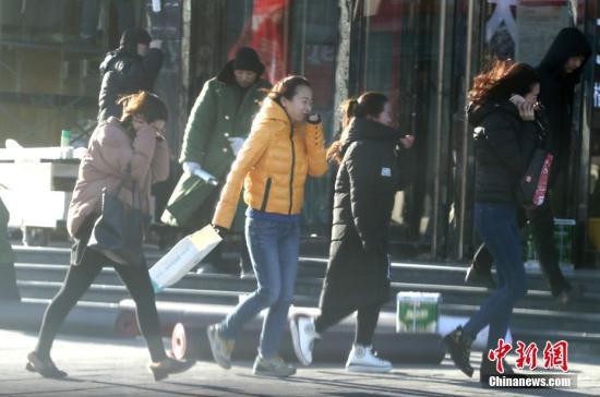 资料图:北京大风降温,市民迎风出行。<a target='_blank' href='http://www.chinanews.com/'>中新社</a>记者 张宇 摄