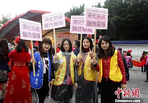 """12月16日,""""两岸交流30年踩街嘉年华""""在台北举走。上千名大陆配偶身着艳服、手执彩旗,走上台北主要街道,外达""""两岸一家亲,牵手心连心,强化交流,融相符发展""""等诉求。 中新社记者 杨程晨 摄"""