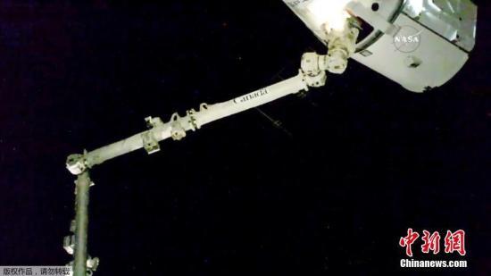"""资料图片:""""龙""""飞船飞临国际空间站,成功被国际空间站机械臂捕获。"""