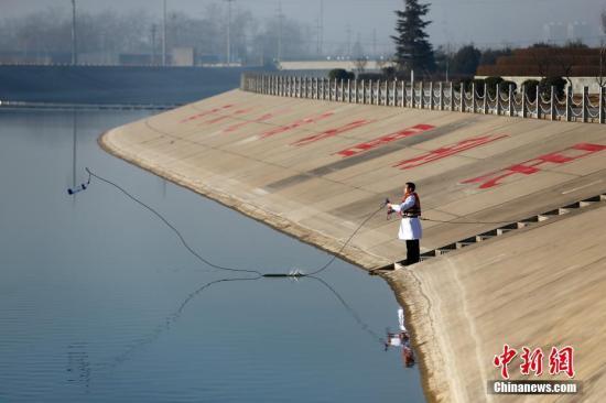 资料图:工作人员为水质监测取水。中新社记者 富田 摄