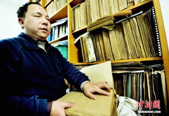 图为江西省德兴市盲人按摩医生马高亮正在触摸有关盲文医学书籍。卓忠伟 摄