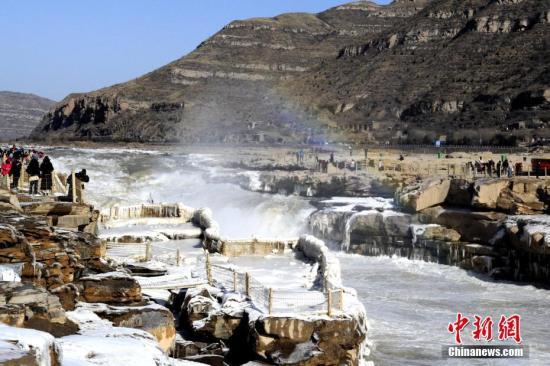 """12月19日,当地气温已降至零下10℃。由于冬季黄河水位回落,壶口瀑布河宽收窄,飞流直下,溅起水雾。在阳光的照射下,形成""""彩虹通天""""的美丽景象。晶莹剔透的冰挂与瀑布上空的彩虹交相辉映。 中新社记者 高庆国 摄"""