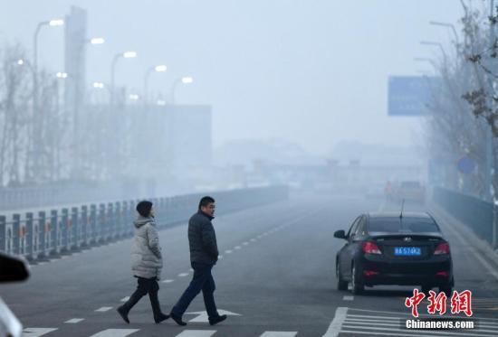 12月20日傍晚时分,华灯初上的新疆乌鲁木齐市依旧被雾霾天气所笼罩,外出民众脚步匆匆。据环保部网站全国城市空气质量小时报数据显示:当日18时,乌鲁木齐市AQI指数为266,首要污染物为PM2.5,空气质量级别为重度污染。 中新社记者 刘新 摄