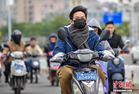 """12月20日,海口民众""""全副武装""""出行抵御冷空气。 记者 骆云飞 摄"""