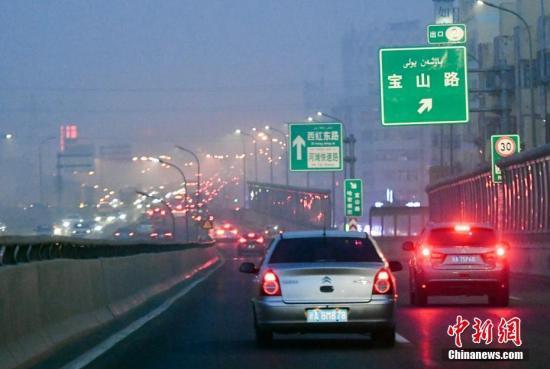 12月20日傍晚时分,华灯初上的新疆乌鲁木齐市依旧被雾霾天气所笼罩。 中新社记者 刘新 摄