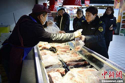 资料图:执法人员取样、抽检肉类。 中新社记者 刘文华 摄