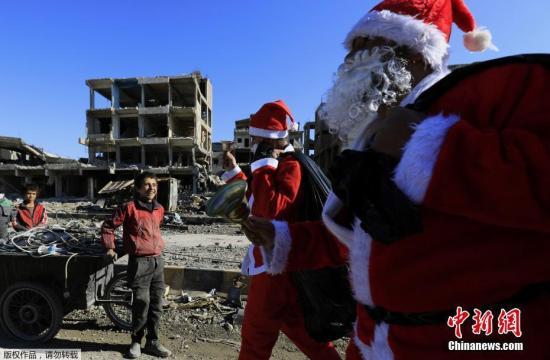 当地时间2017年12月26日,叙利亚军事委员会(SMC)成员和叙利亚民主力量的成员参加了一场圣诞节庆祝活动,士兵们装扮成圣诞老人,在拉卡市的废墟里穿行,给人们送去温暖。