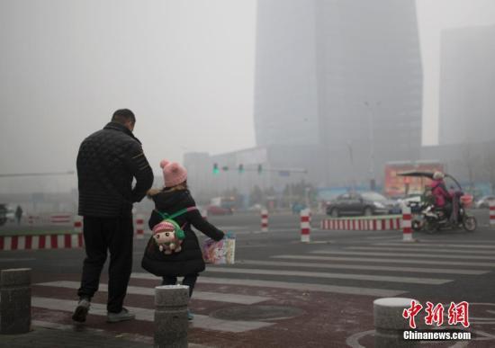 资料图:市民在雾霾中出行。中新社记者 刘关关 摄