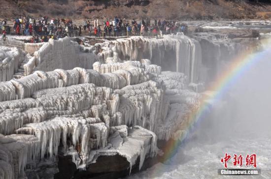 12月31日,游客在山西吉县黄河壶口瀑布欣赏冰瀑景观。中新社发 汪小英 摄 图片来源:CNSPHOTO