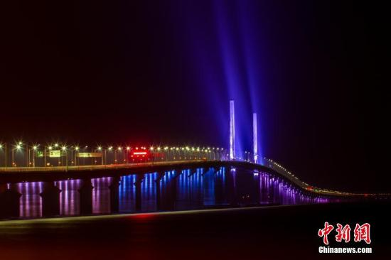 """12月31日,港珠澳大桥全线亮灯,标志着全线供电照明系统施工圆满完成,意味着港珠澳大桥主体工程已经具备通车条件。亮灯仪式上,大桥东人工岛四周燃放起壮丽的烟花。图为港珠澳大桥嵌有""""中国结""""的青州桥亮起了灯光。邓媛雯 摄"""