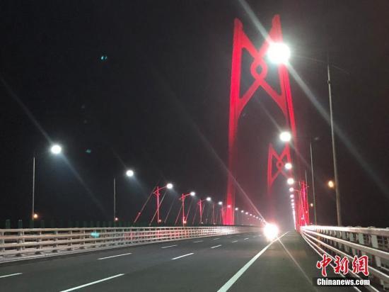 12月31日,港珠澳大桥全线亮灯,标志着全线供电照明系统施工圆满完成,意味着港珠澳大桥主体工程已经具备通车条件。亮灯仪式上,大桥东人工岛四周燃放起壮丽的烟花。图为港珠澳大桥主体31日晚全线亮灯。邓媛雯 摄