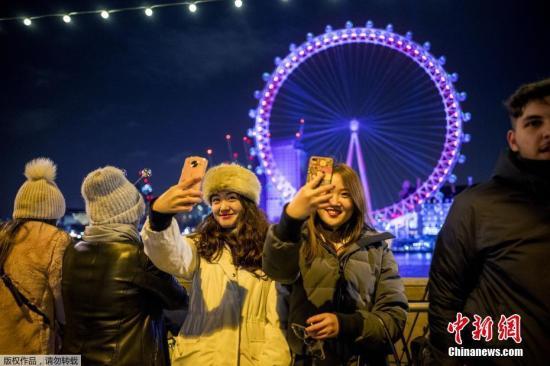 资料图:2017年12月31日,民众聚集在在英国伦敦眼前迎接新年到来。