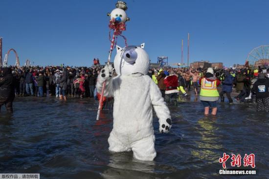 """当地时间2018年1月1日,纽约民众聚集在科尼岛,参加""""北极熊跳水""""庆新年活动,虽然海水冰冷刺骨,但参观活动的人们乐在其中,欢庆新年到来。图为一名打扮成北极熊的参与者站在海水中,等待活动开始。"""