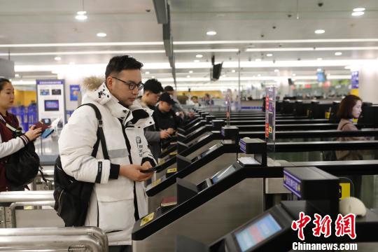 资料图:旅客在浦东机场T2航站楼出境大厅内,扫登机牌、刷护照、按指纹拍照片,10多秒就能自助出境通关。殷立勤 摄