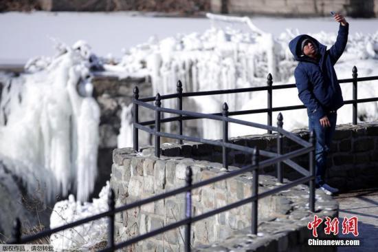 美国国家气象局气象学家布赖恩・赫尔利说,今后两天全美可能20多个地方会刷新低温纪录。图为当地时间1月2日,新泽西州东北部城市帕特森的居民Obdulio Arenas举起手机自拍,在他身后是在极寒天气中冻住的瀑布。