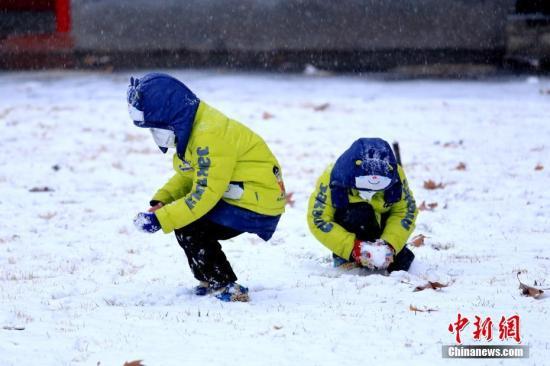 西安迎2018年初雪,小朋友在玩雪。王晓凯 摄