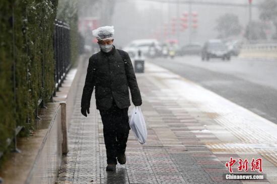 1月3日,陕西西安,一名行人冒雪出行。受强冷空气影响,陕西迎来大范围降雪天气。<a target='_blank' href='http://www.chinanews.com/'>中新社</a>记者 张远 摄