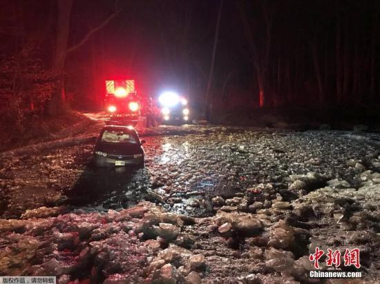 低温造成道路湿滑,引发不少交通事故。图为当地时间1月1日,马里兰州博伊兹的一辆载有3人的车滑入冰水中无法动弹,消防队展开救援。