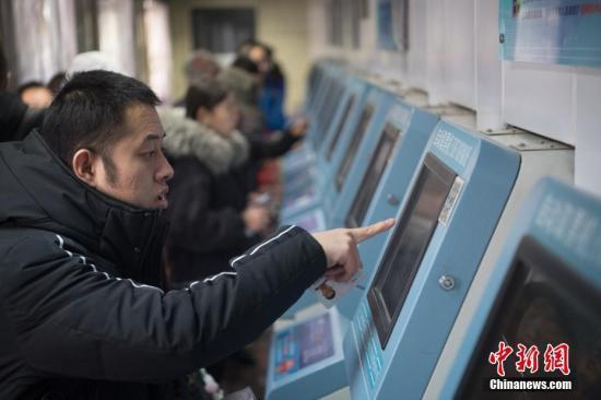 1月4日,山西太原火车站,使用网络购票的旅客在自动取票机上领取火车票。记者 韦亮 摄