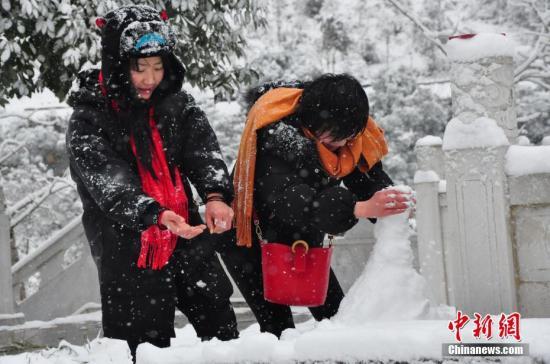 资料图:重庆城口县降下大雪,民众正在堆雪人。王代前 摄