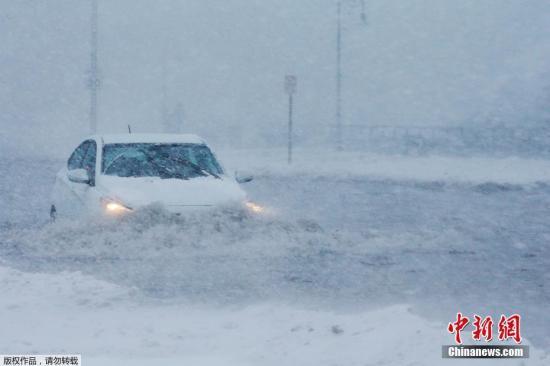"""当地时间2018年1月4日,美国马萨诸塞州波士顿郊区遭暴风雪袭击,海水涌上防波堤将道路变成""""冰河""""。图为波士顿郊区风雪漫天,汽车行驶在积水中。"""