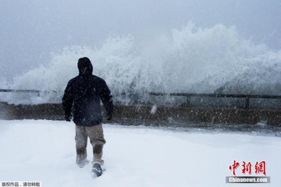 波士顿郊区市民站在海堤边观看波涛奔涌上岸。
