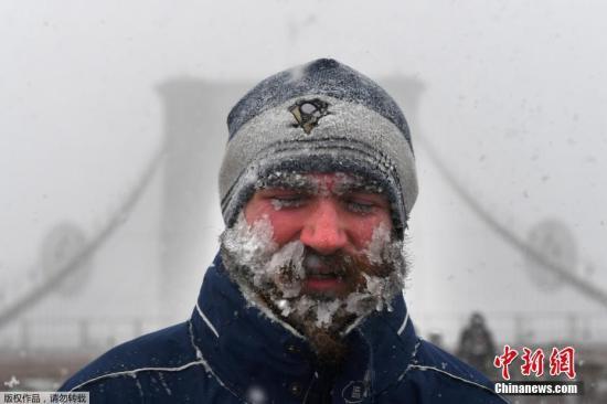 """当地时间1月4日,纽约市迎来2018年首场暴雪。受一波被称为""""炸弹气旋""""的风暴影响,美国东北部地区当天普遍遭受暴雪袭扰,3000多个航班因此取消。图为纽约布鲁克林大桥上,一名行人行走在漫天暴雪中,脸上布满冰碴。"""