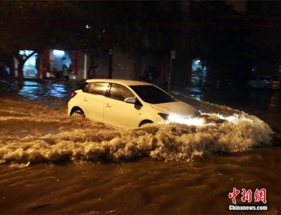 车辆行驶在积水街道中。朱柳融 摄