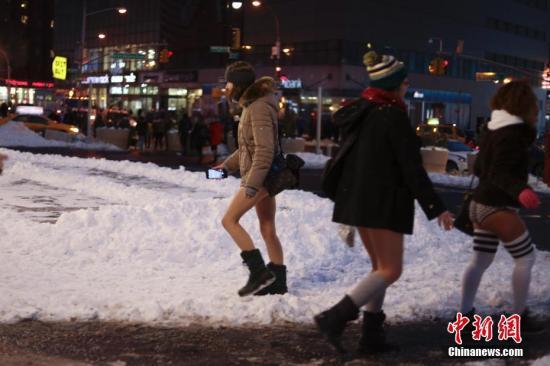 """当地时间1月7日,纽约女子在曼哈顿的地铁里参加""""不穿裤子搭地铁""""活动时穿行雪地。 <a target='_blank' href="""