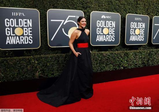 当地时间1月7日,第75届金球奖在美国比佛利山希尔顿酒店举行。今年是金球奖75周年,主办单位好莱坞外国记者协会也花心思选择了金红配色来装饰红毯,到处都是75周年的标志。图为女星曼迪・摩尔。