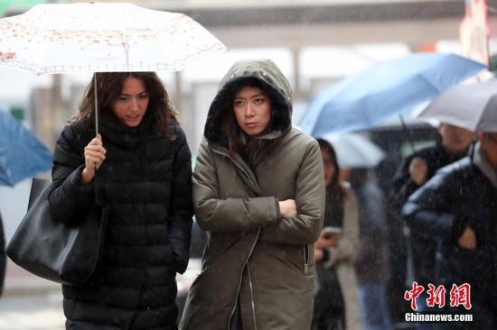 资料图:香港市民在蒙蒙细雨中出行。中新社记者 洪少葵 摄