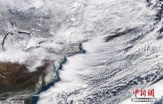 """美国国家航空航天局(NASA)于2018年1月6日发布的一幅卫星图,图为拍摄到的一场席卷加拿大安大略湖、加拿大东部和美国东北部的冬季暴风雪。 美国国家气象局最新通报说,寒冷天气预计持续至7日。用俄克拉荷马大学气象学教授佛塔多一句话来描述2018年初美国人的这波""""三九天"""":将以刺骨的严寒结束。"""