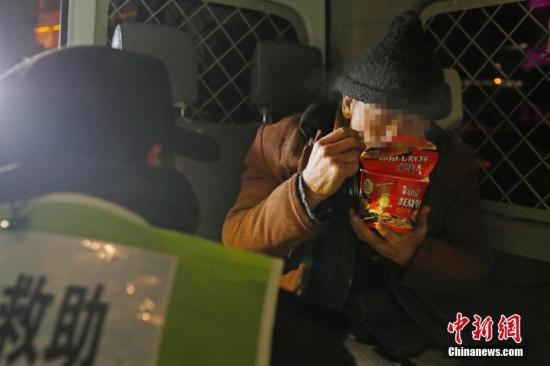露宿街头人员在车上吃着泡面,准备前往救助站避寒。中新社记者 殷立勤 摄