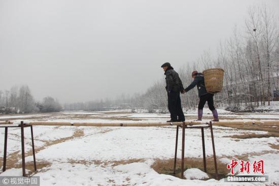 """陕西城固县两村庄67名学生靠简易竹桥通行上学,雪后桥面结冰,危险难行,当地民众盼望建一座""""安全桥""""。张映伟 周金柱 摄 图片来源:视觉中国"""