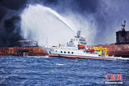 """1月12日上午10时25分,""""桑吉""""轮与""""长峰水晶""""轮碰撞事故现场灭火作业第三次启动。图为""""东海救117""""轮向""""桑吉""""轮喷射泡沫降温灭火。1月6日19:51时左右,巴拿马籍油船""""桑吉""""轮与中国香港籍散货船""""长峰水晶""""轮在长江口以东约160海里处发生碰撞。中新社发 上海海上搜救中心供图"""
