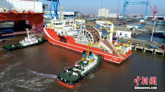 """1月12日,在大马力拖轮的协助下,先进深海原油转驳船""""SeaLoader1""""缓缓从江苏启东中远海工码头驶出,前往海域进行试航。据介绍,该船总长约90米,型宽约20米,生活区可供36人居住。全船采用可变速柴油机、直流电站系统,可显著提高燃油经济性,将开创全新的海洋油田原油转驳方式。该船是由南通中远船务工程有限公司为挪威船东Sealoading设计建造,具有很强的动力定位能力,便于大型油船定位在安全作业的海域,可将FPSO(浮式生产储油船)上的原油快速安全地转驳到常规油船上。 陈福广 摄"""