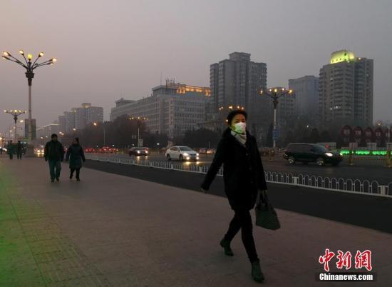 1月13日,北京市民在雾霾中出行。北京市空气重污染应急指挥部于11日晚发布2018年首个空气重污染橙色预警,称将于1月13日0时至1月15日24时实施橙色预警措施。中新社记者 刘关关 摄