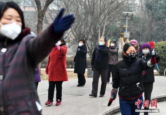资料图:河北石家庄遭遇严重雾霾天气。图为市民戴口罩健身。中新社记者 翟羽佳 摄